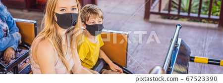 Mom and son on a roller coaster in medical masks after the coronovirus epidemic COVID 19 BANNER, LONG FORMAT 67523390