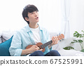 A young man practicing the ukulele 67525991