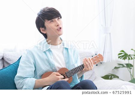 一個年輕人練習夏威夷四弦琴 67525991
