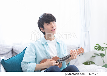 A young man practicing the ukulele 67525992