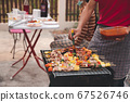 A man grilling pork and barbecue in dinner party. 67526746