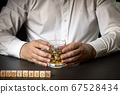 Man with a glass of Scotch and ice and the word 67528434