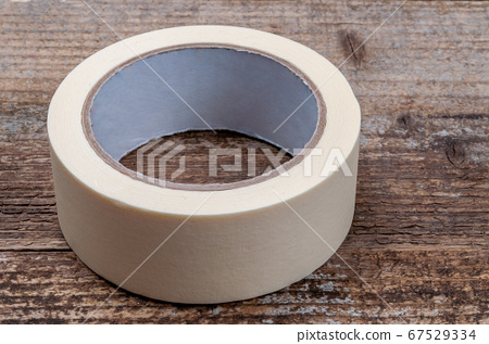 Masking tape on wooden background. Repair tool. 67529334