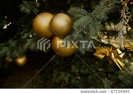 Big golden Christmas flasks hanging from Christmas tree 67530995