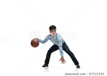 Man in office clothes playing basketball on white background. Unusual look for businessman in motion, action. Sport, healthy lifestyle. 67531785