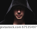 Close-up portrait of a courageous man in a deep dark hood on a black background. The concept of secrecy of secrets and people hiding from the government. Hackers and thieves. Low key 67535497