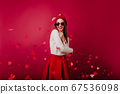 Emotional young woman in red hat and sunglasses 67536098