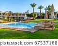 Luxury resort with swimming pool, sun loungers and beach umbrellas. Oriental tropical hotel in Egypt 67537168