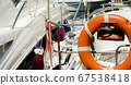 Orange lifebuoy on the side of the boat, an 67538418