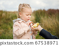 Little girl admires the little duckling held by mom's hand 67538971
