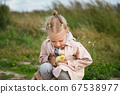 Little girl with little duckling outdoors 67538977