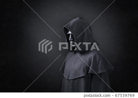 Scary figure in hooded cloak in the dark 67539769