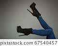 Female legs in high boots, isolated on gray background 67540457