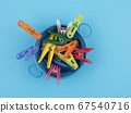 Colored clothespins in the bowl on a blue 67540716