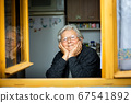 Portrait of lovely senior woman or grandmother watching out from the window and smiling, pensioner 67541892