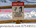 Caution sign on wooden fence against snow 67548551