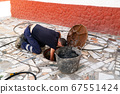 Worker cleans the drains hatch and removes dirt and debris from the sewer. Plumber cleans the sewer 67551424