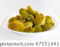 Boiled yellowed broccoli on a white plate. Inflorescence boiled broccoli. Close-up view 67551441