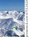Paragliding at snowy mountains over ski resort 67551620