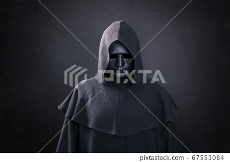Scary figure with mask in hooded cloak in the dark 67553084