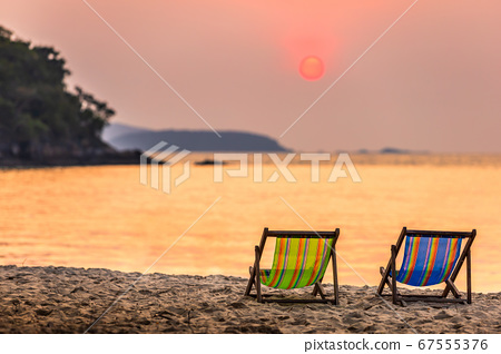 Beautiful early sunset over two deck chairs on the 67555376