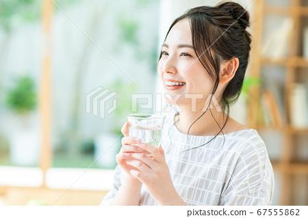 年輕女子在客廳裡喝礦泉水 67555862