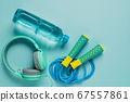 Fresh drinking water, jump rope and headphones on blue background 67557861