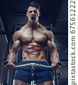Bodybuilder strong man pumping up biceps muscles 67561222