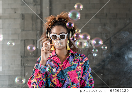 Black lady in headphones blowing bubbles 67563129