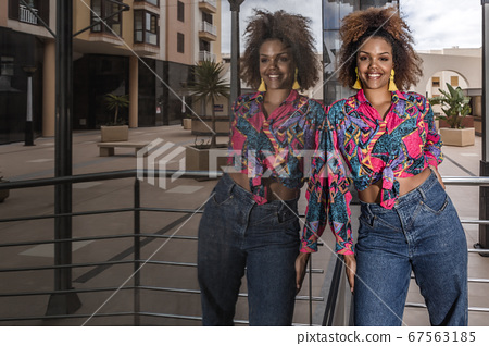 Happy ethnic woman in trendy wear standing near 67563185