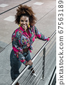 Happy ethnic woman in stylish outfit standing on 67563189