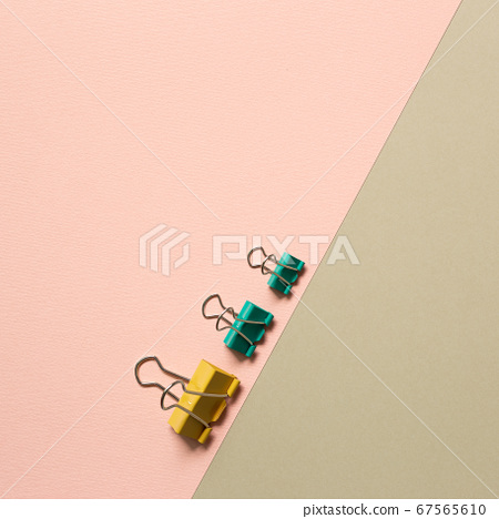 Yellow and green metal binder clips on pink and beige background. top view 67565610