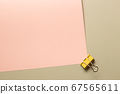 Yellow metal binder clip on pink and beige background. top view 67565611