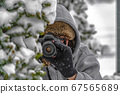 Photographer behind a snow covered tree in winter 67565689