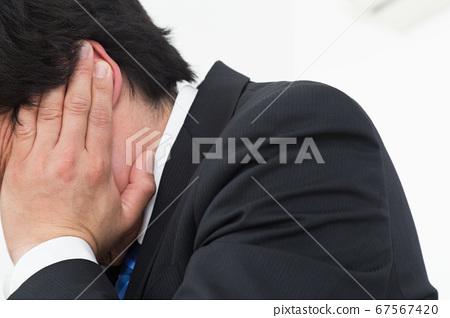 Office worker holding ears 67567420