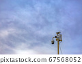 Outdoor security camera isolated against a cloudy 67568052