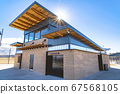 Blue sky and bright sun over a park building with 67568105
