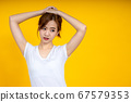Asian woman gathering her hair over yellow 67579353