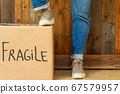 Moving box with the word Fragile near wooden wall, two legs with jeans and sneakers in retro room new house and moving concept 67579957