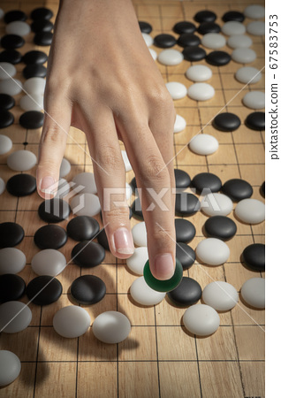 close up of player hand with weiqi stone to make a 67583753