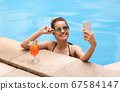 Lovely Caucasian girl taking selfie on smartphone in pool at tropical resort 67584147