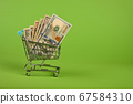 US dollar banknotes in shopping cart over green 67584310