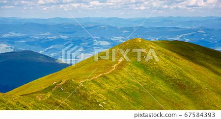 trail uphill through mountain range. grass on the 67584393