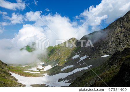 high mountain peaks among the clouds. wonderful 67584400