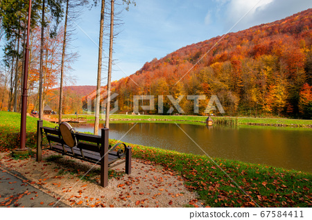 small lake in autumn park. forest on the hills in 67584411