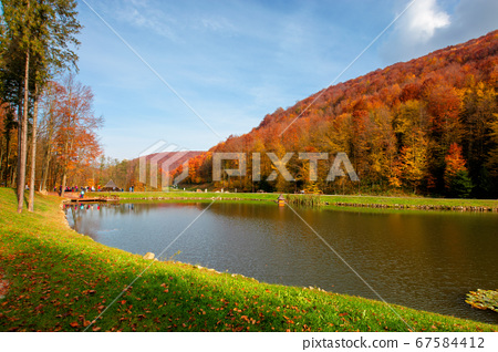 small lake in autumn park. forest on the hills in 67584412