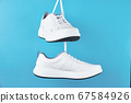 Pair of white male sneakers on blue background. 67584926