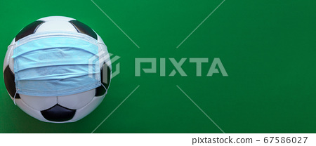 Sport, football, competitions, physical culture, healthy lifestyle, covid-19 concept - banner closeup black and white soccer ball in protective mask on plain green background chromakey copy space. 67586027