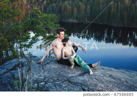 middle age man with little cute son doing sport yoga on the top of the mountain together, happy family lifestyle people outdoor, summer wild nature for training 67586885