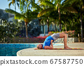 A man practice yoga near to swimming pool 67587750